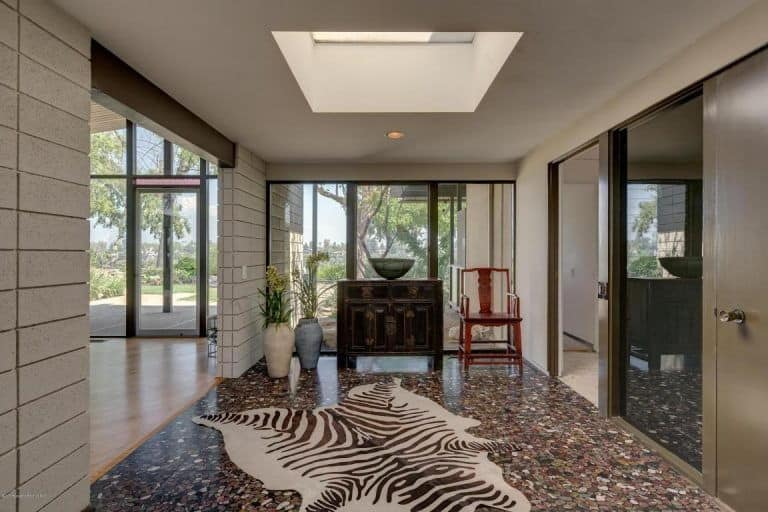 This celebrity foyer has a beautiful zebra fur area rug in the middle of the complex earthy flooring. This goes well with the gray concrete walls of the entryway and the brown waist-high cabinet on the far glass wall. This glass wall brings in brightness along with the skylight in the middle of the light gray ceiling.