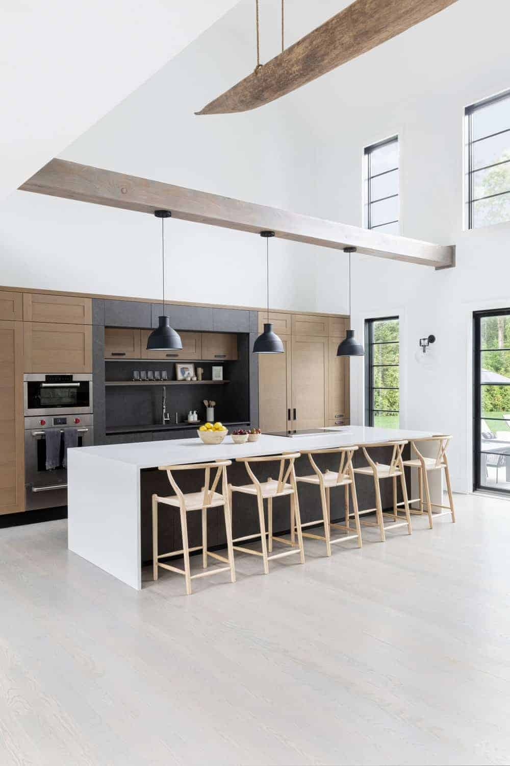 The home features a single wall kitchen with brown cabinetry along with a white breakfast bar countertop lighted by pendant lights.
