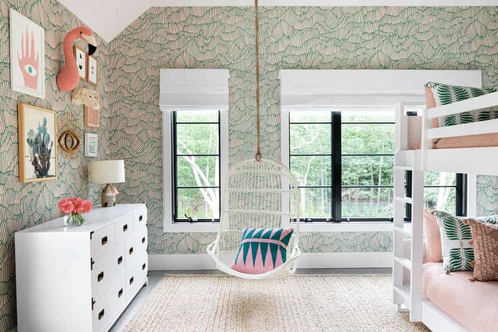 The kids' bedroom boasts elegant-looking and very attractive walls along with a white side cabinet and table.