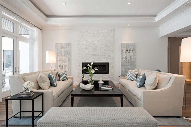 This is a simple yet elegant living room with a couple of beige cushioned sofas flanking a large dark wooden coffee table with a modern fireplace at the far wall.