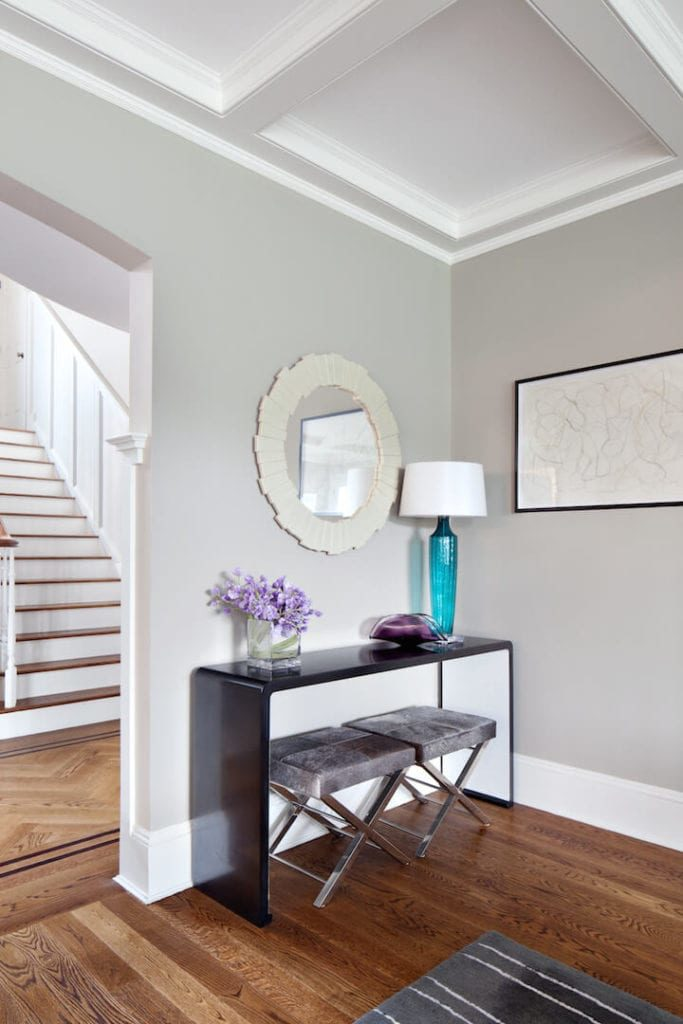 This is a simple and homey Contemporary-style foyer with a white coffered ceiling to complement the gray walls. This makes the black console table stand out with its small modern stools, glass table lamp and decors along with a circular white mirror.