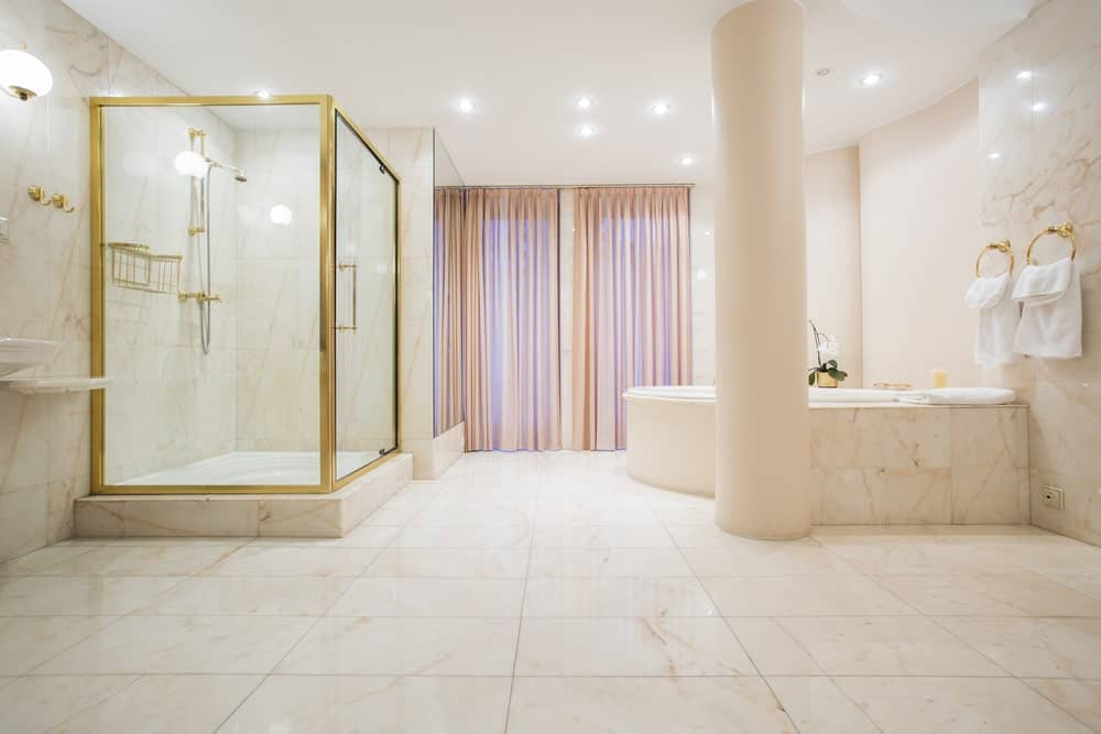 Large master bathroom with lovely marble tiles floors and walls. The corner bathtub and shower both look glamorous.