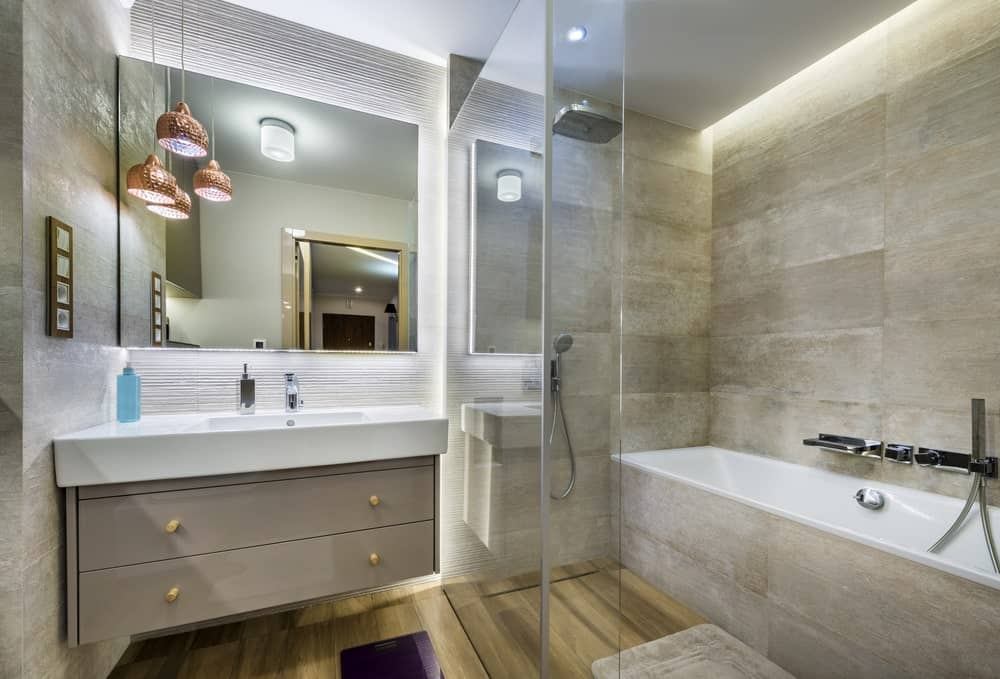 This master bathroom boasts stylish walls and floors. The floating vanity sink looks classy together with the bathtub and corner shower.