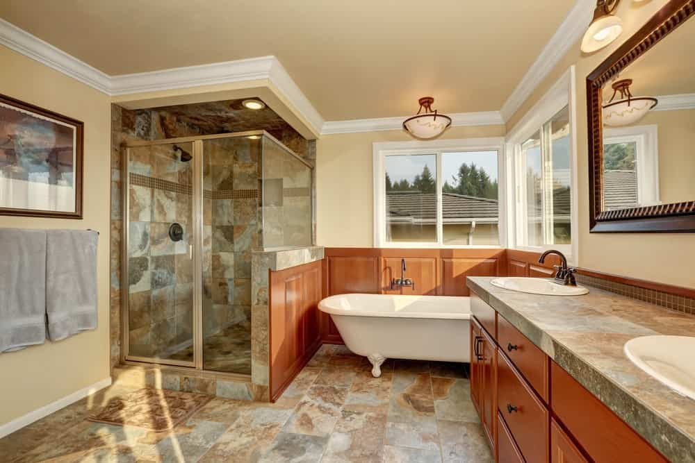 Large master bathroom with a corner shower surrounded by glamorous tiles walls and floors. There's a freestanding tub on the corner as well.