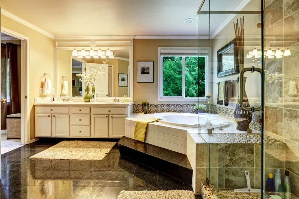 Large elegant master bathroom with stylish tiles flooring and glamorous lighting. The bathtub looks classy while the shower room looks so nice as well.