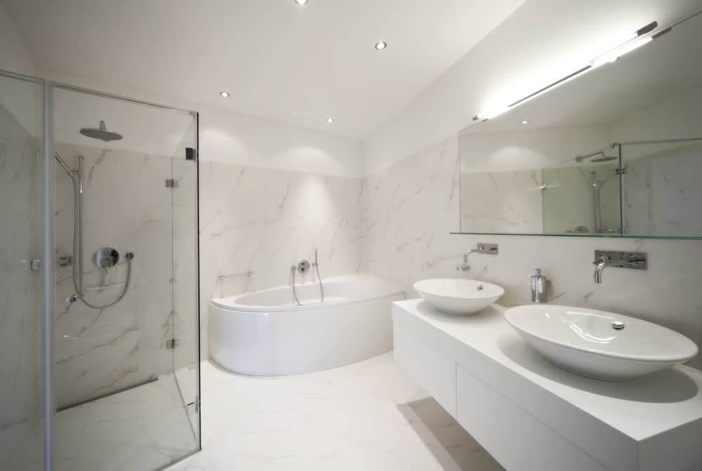 Large master bathroom boasting marble walls and floors. It also offers a classy bathtub and a corner shower area, along with a floating vanity with two vessel sinks.