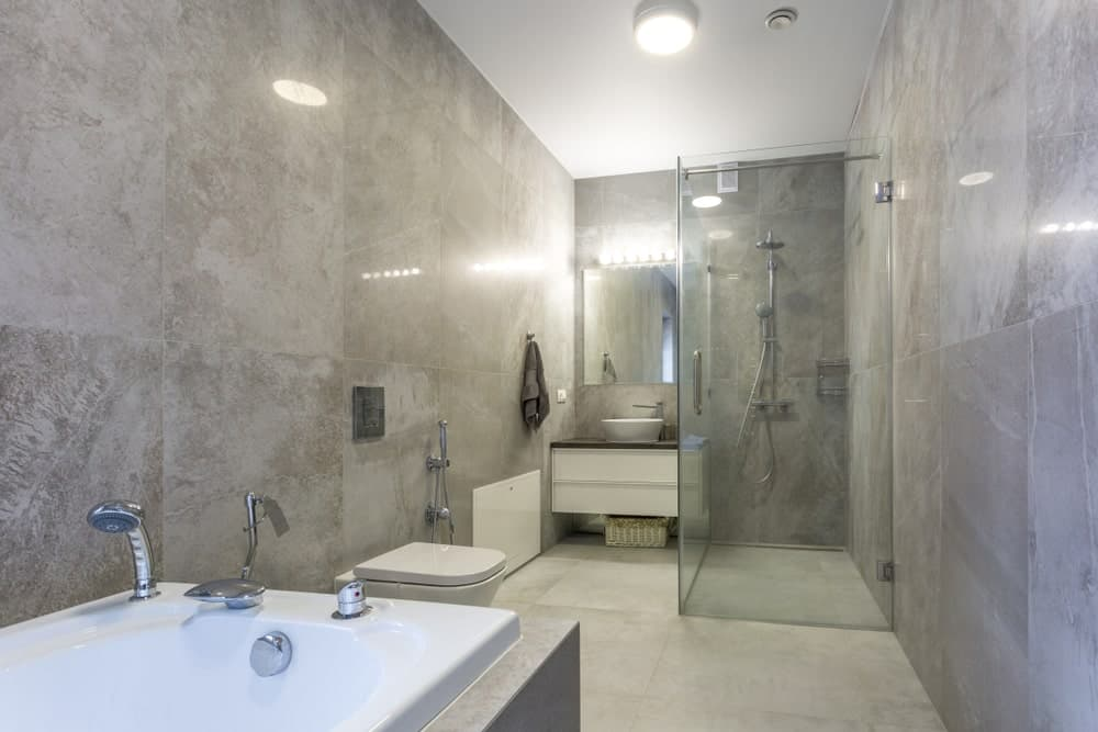 This bathroom boasts stylish walls and floors. It also offers a walk-in shower, a vessel sink and a bathtub.