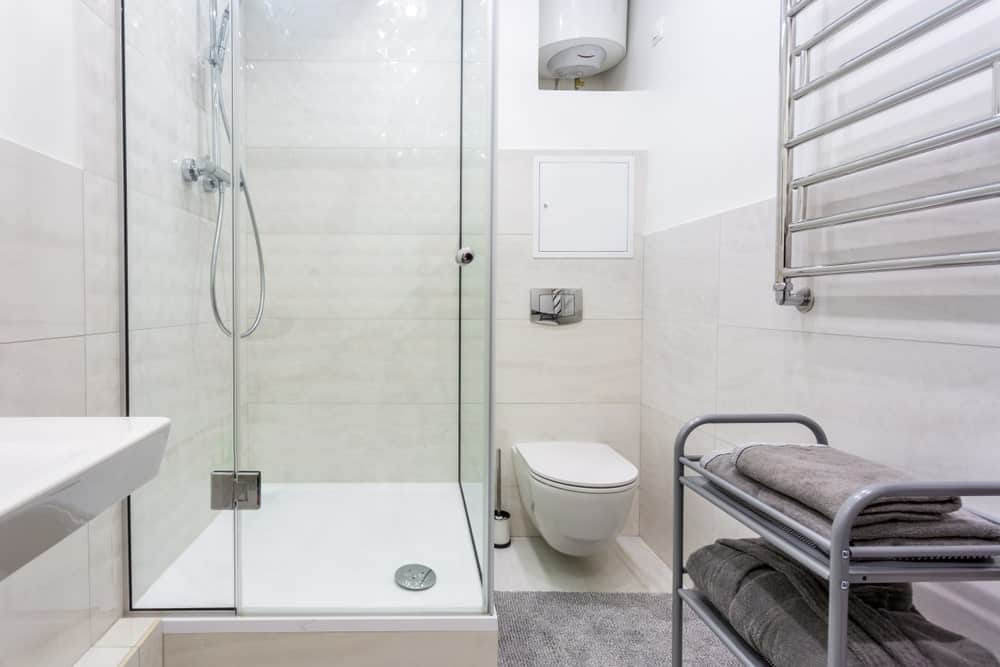This master bathroom offers a corner shower room. It also features tiles flooring and walls.