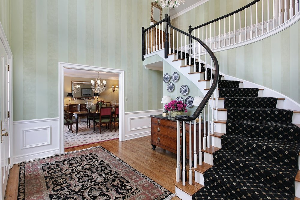 This Country-style foyer has white wainscoting to complement the subtle striped light gray wallpaper. This makes the dark patterned carpeting of the stairs stand out along with the dark banister of the white wooden railings that extend to the second floor.