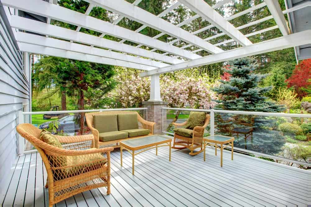 This deck offers a classy set of seats and tables. The surrounding plants and trees look so glamorous.