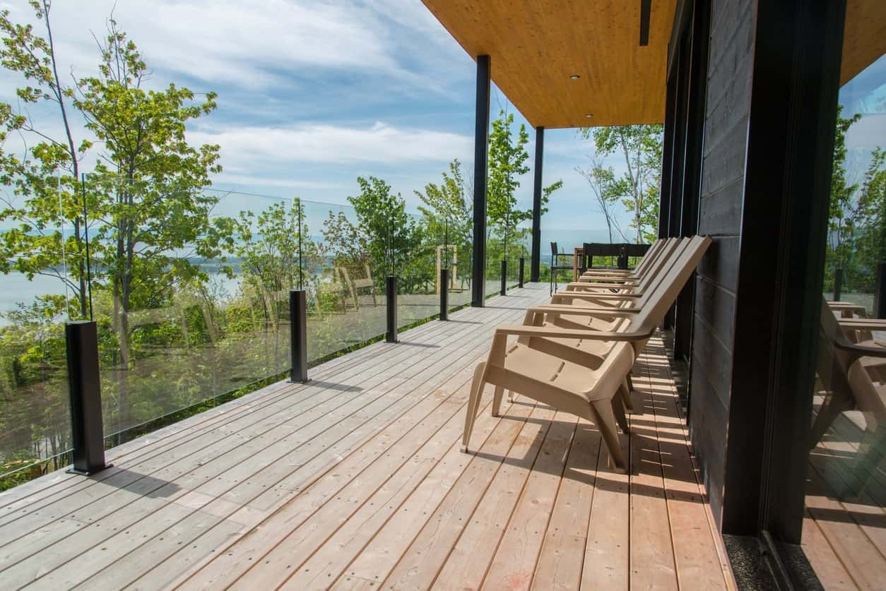 Large deck featuring multiple lounging seats and glass railings overlooking the beautiful surroundings.