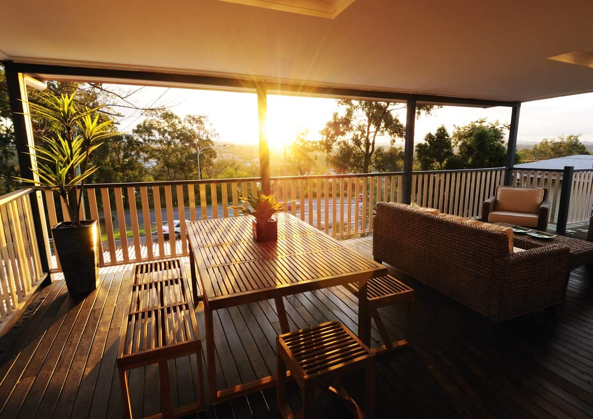 Simple covered deck with a wooden dining table set and rattan sofa set with cushion seats and foam backrests.