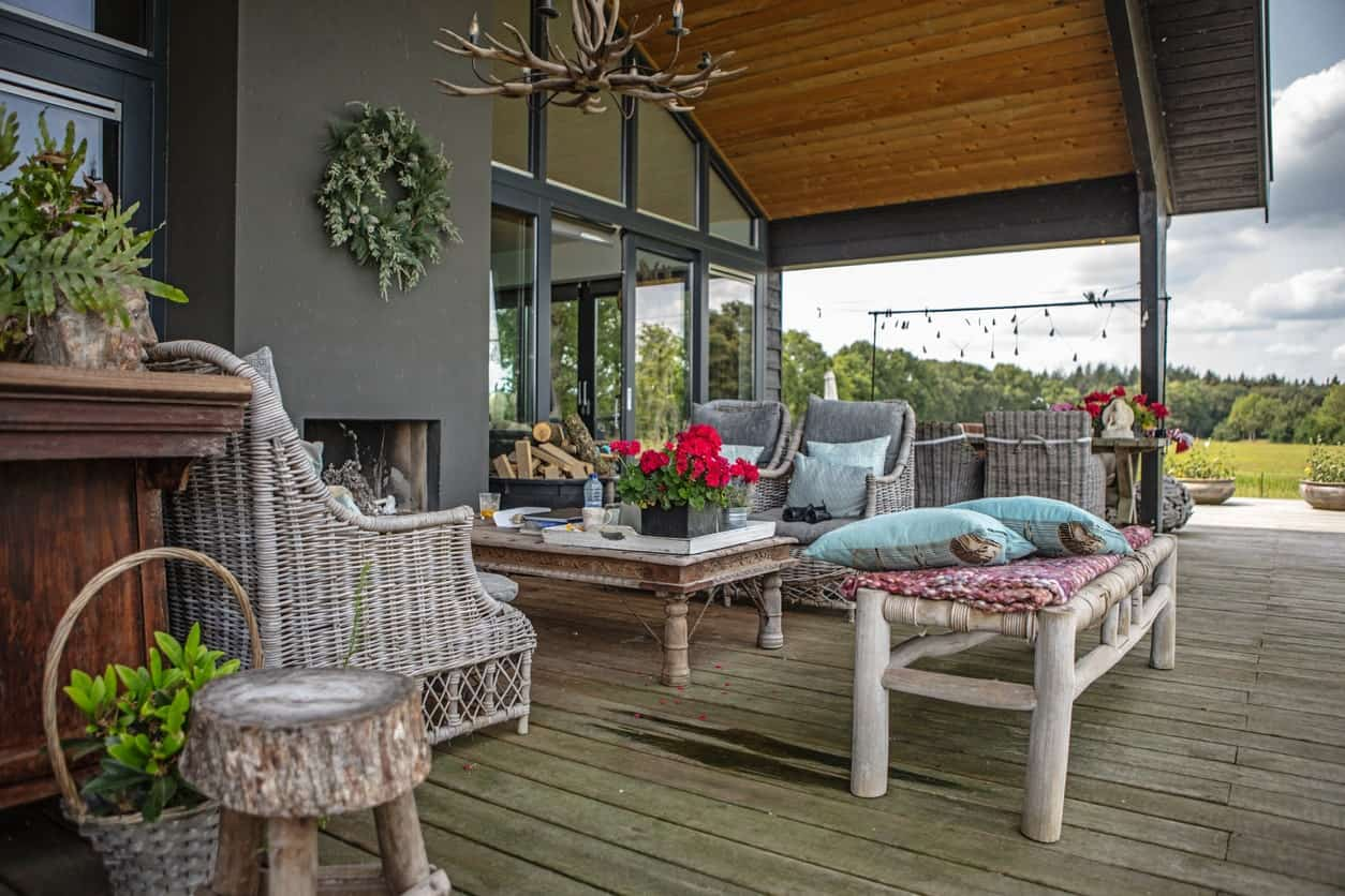 Large deck featuring an outdoor sofa set near the fireplace.