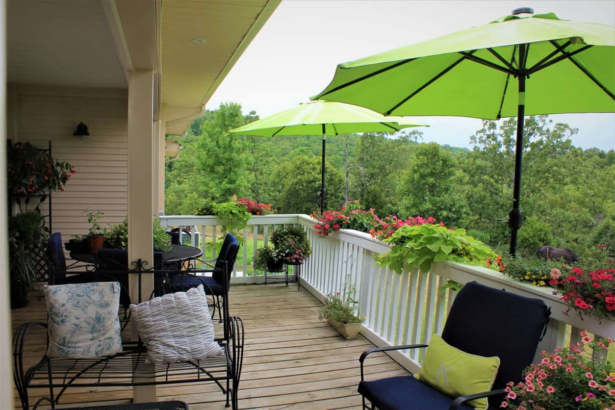 This deck has a small dining table set and lounging seats shaded by a couple of umbrellas.