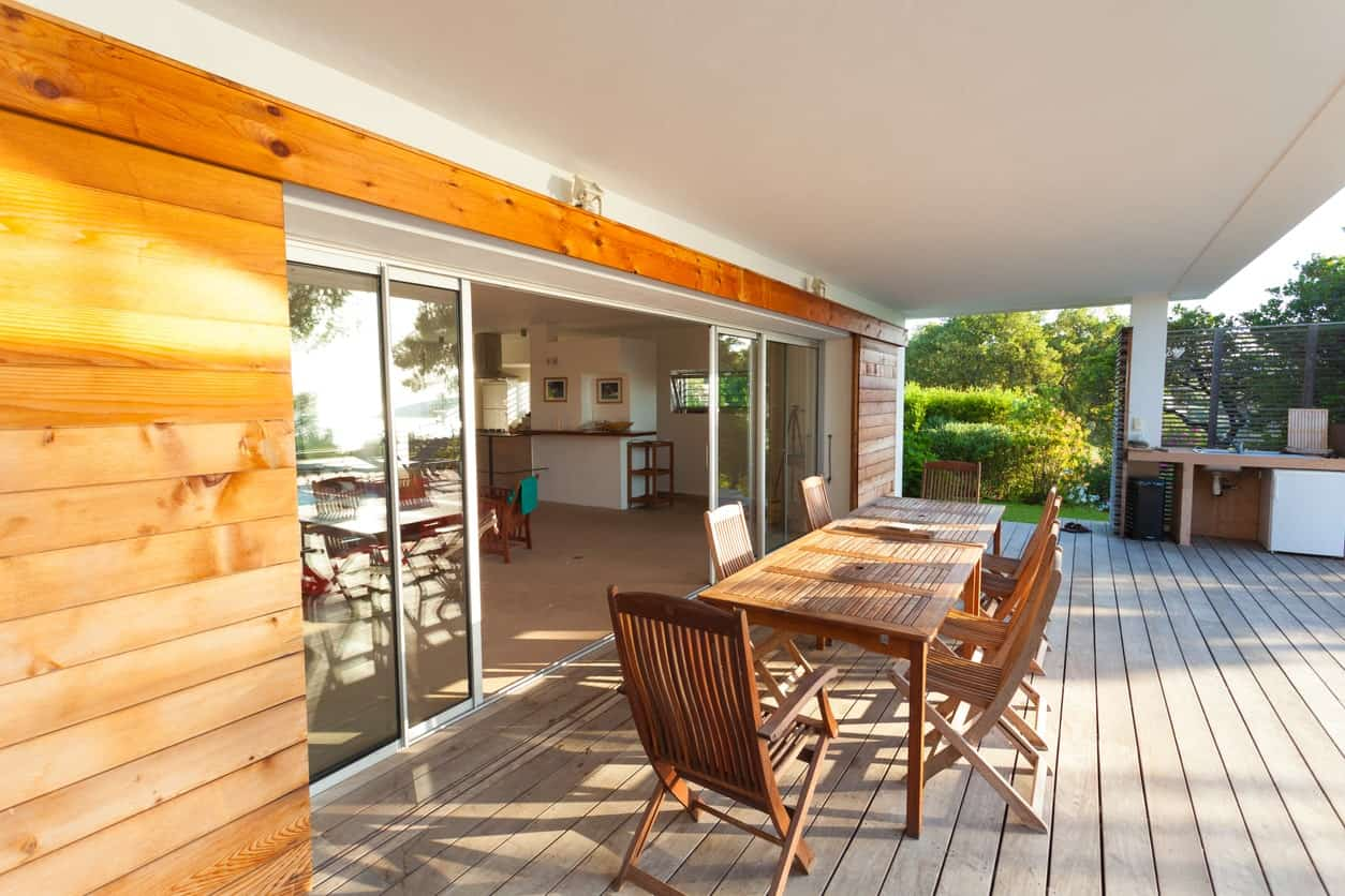 A covered deck offering a large wooden dining table set.