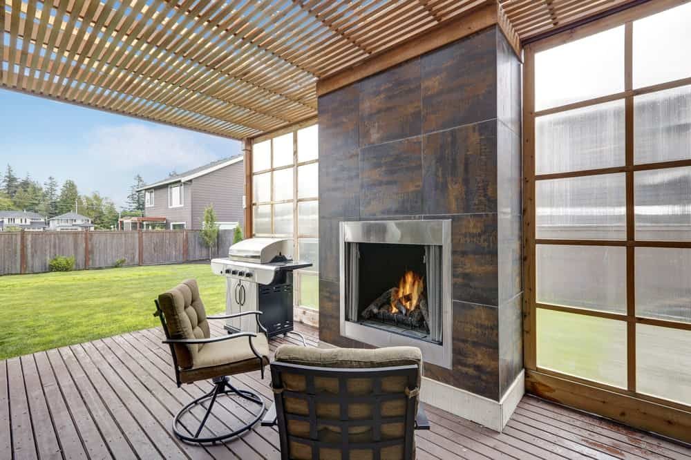This deck boasts modern seats in front of a stylish fireplace.