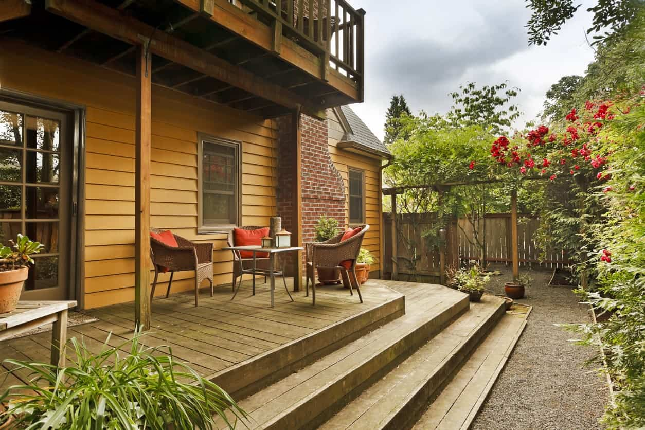 Small deck patio surrounded by beautiful plants and flowers.