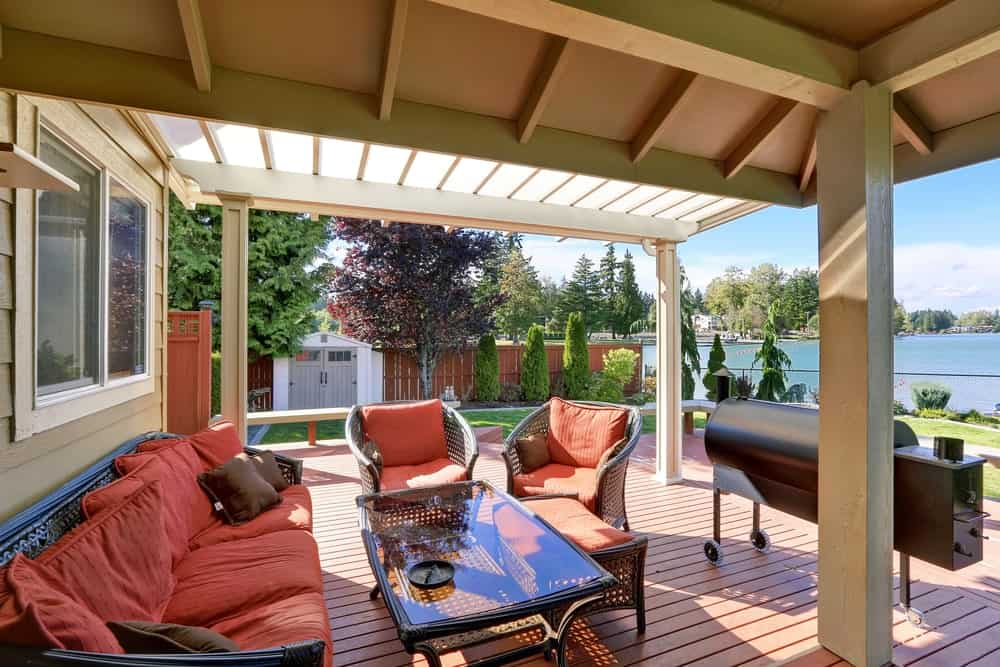 Covered deck featuring a cozy set of seats overlooking the beautiful river surrounding the area.