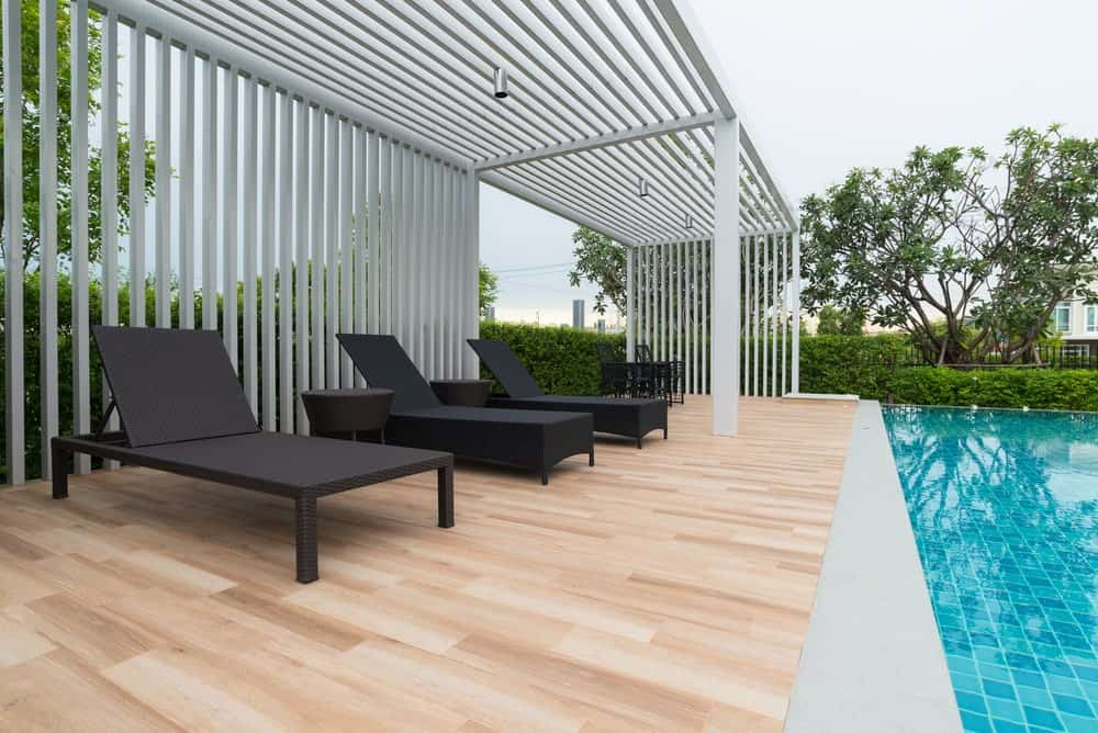 Pool-side deck boasting a set of dark finished rattan lounging seats.