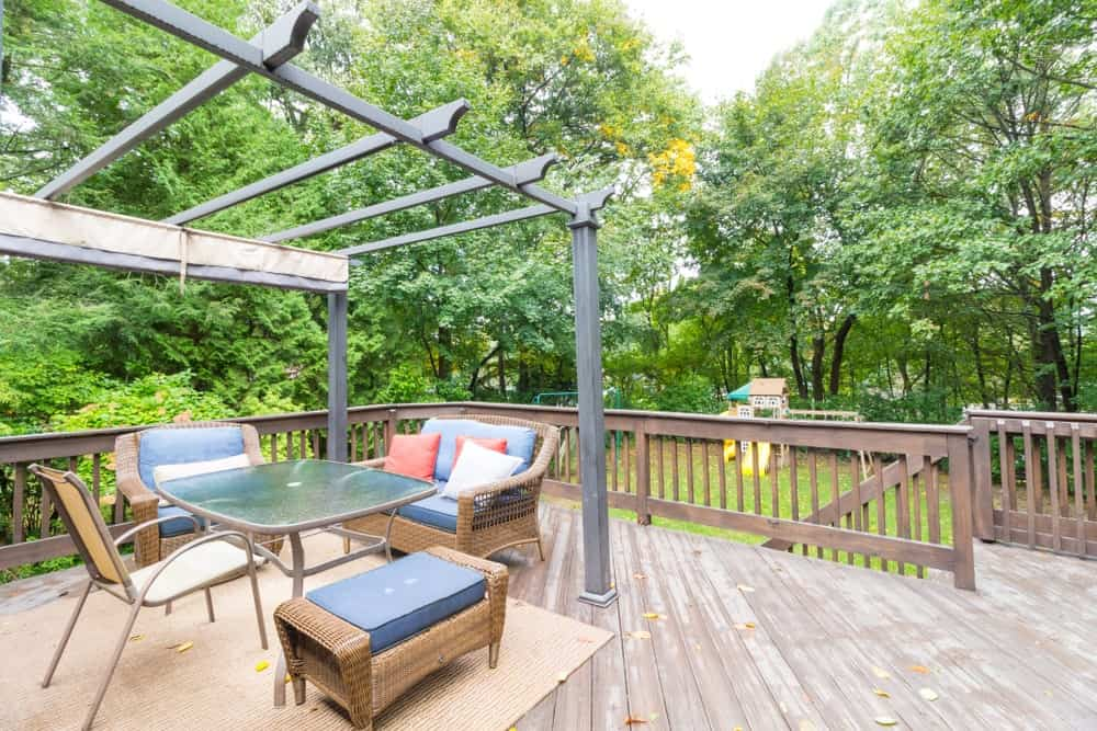 Large deck patio area surrounded by beautiful plants and trees.