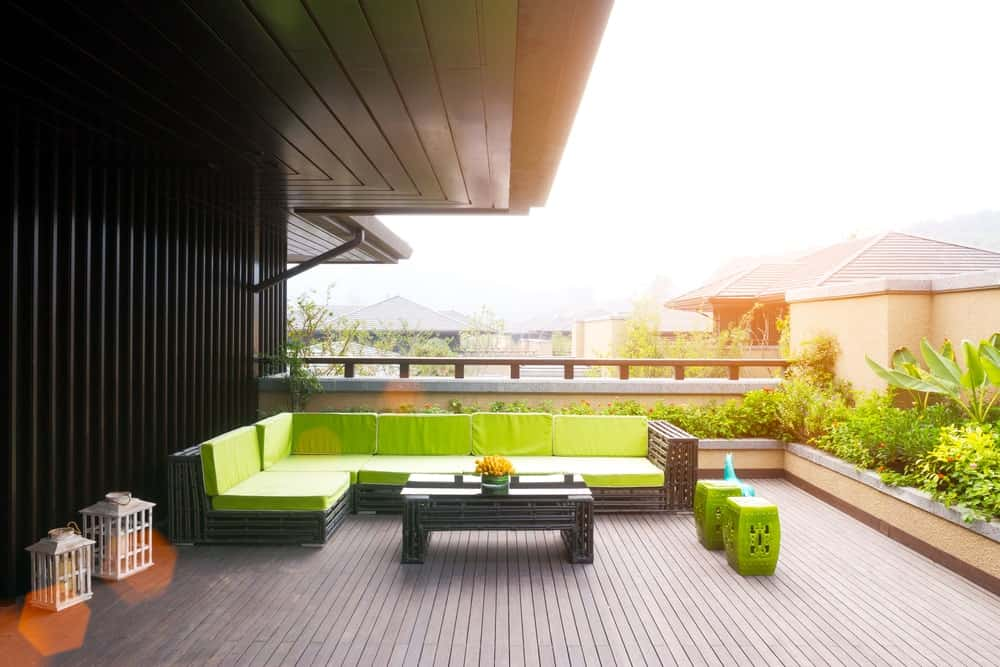 This deck offers a long L-shape outdoor sofa set with green seats and backrests matching the surrounding green plants.