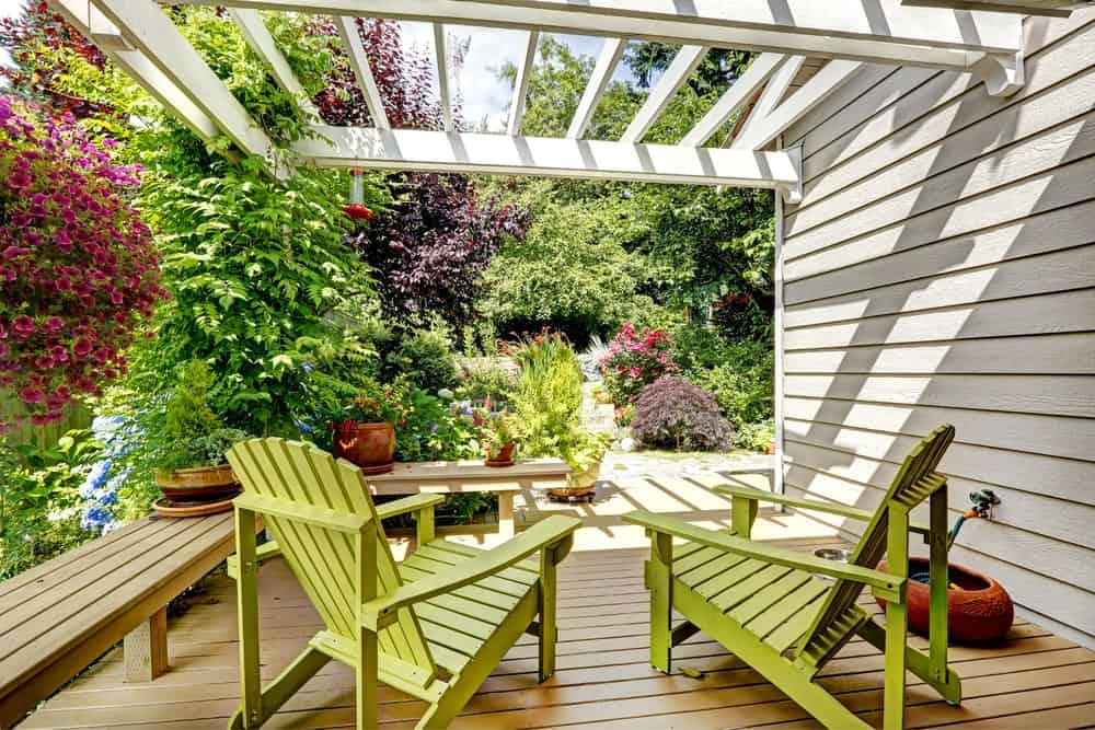 This deck with wooden loungers and bench is surrounded by lovely flowers and greens.