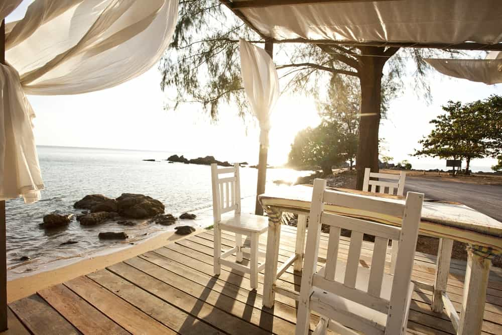 A sea-side deck with a small dining table set overlooking the stunning ocean view.