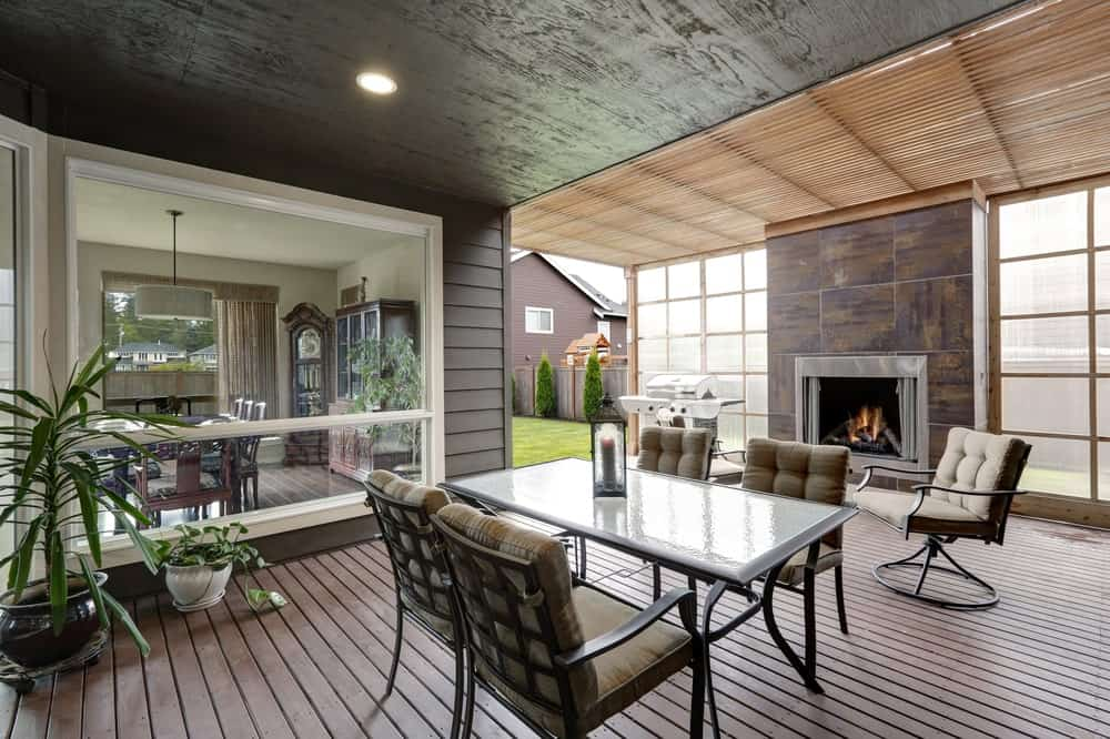 Modern covered deck with a small dining table set and a fireplace.