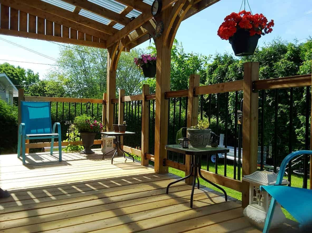 This deck features an iron railing with wooden frame.