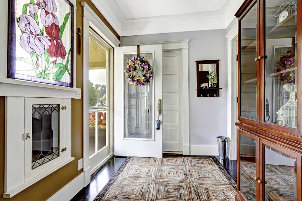 This simple and homey Craftsman-style foyer showcases the primaryful wooden structures that give this foyer a unique look like the wooden door, ceiling and the dark brown wooden cabinet with glass panels for decors. Across from this is a brilliant stained glass window.