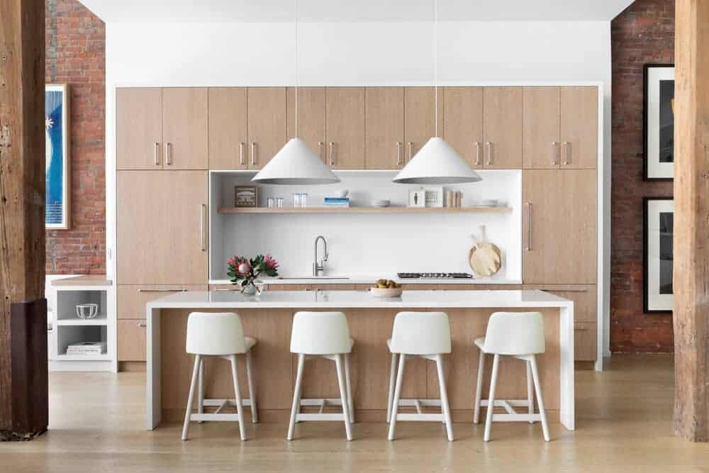 A focused shot at this industrial-style kitchen with a large center island featuring space for a breakfast bar, lighted by two pendant lights.
