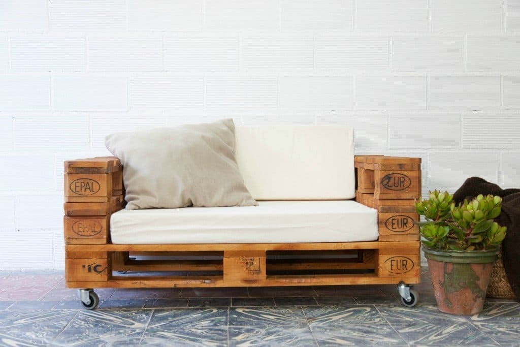 Attractive pallet loveseat with arms and white cushions
