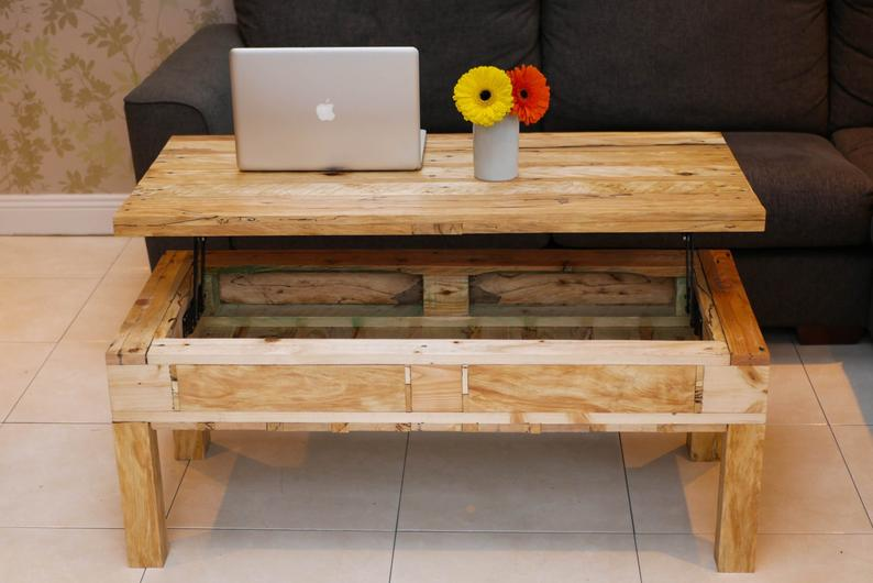 Custom-built natural wood lift-top pallet coffee table with storage underneath.  This design includes table legs.