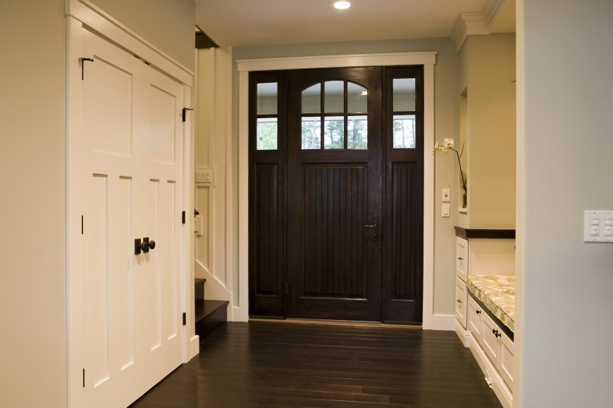 This simple Farmhouse-style foyer has a comfortable sitting area for the guests beside the dark wooden main door that matches with the dark hardwood flooring. The sitting area has a built-in wooden white bench with a patterned cushion.