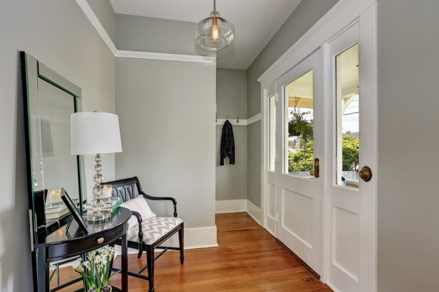 The small and compact foyer has gray walls that makes the dark wooden elements stand out like the armchair and console table adorned with a large mirror. These are all topped with a simple glass spherical pendant light hanging from the white ceiling.