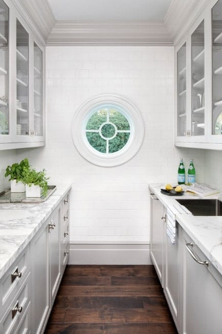 This galley kitchen offers white cabinetry, white counters and marble countertops, along with the hardwood flooring.