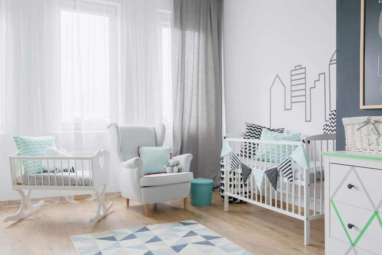 Nursery room with white walls and curtains along with gray and green pillows matching the rug.