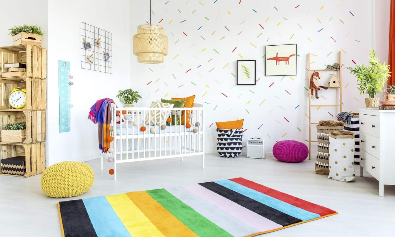 This nursery room features a colorful wall and rug along with cute decors.