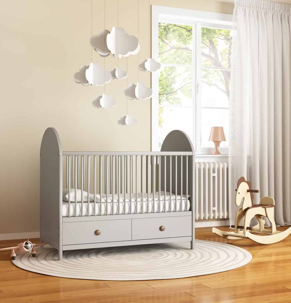 Beige nursery room with an interesting rug, gray crib, and a hardwood flooring.