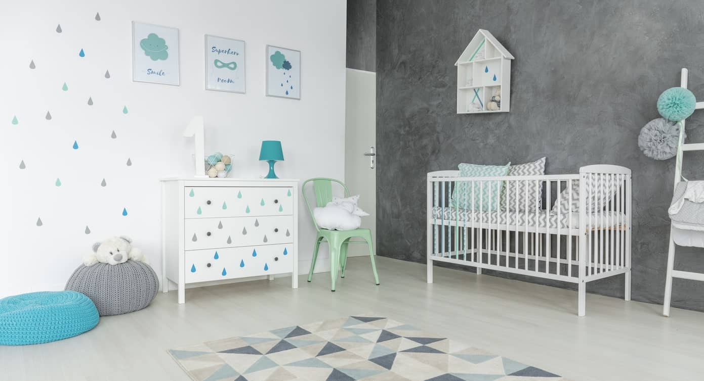 Contemporary nursery room with white and gray walls and has a stylish rug.