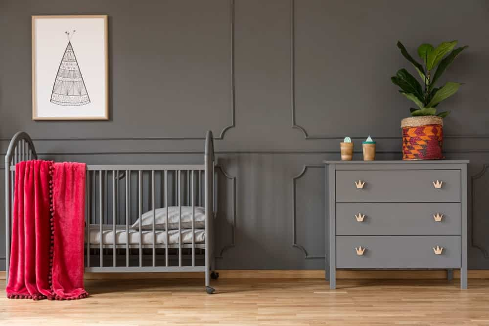 Nursery room with dark gray walls matching the crib and side table set on the hardwood flooring.