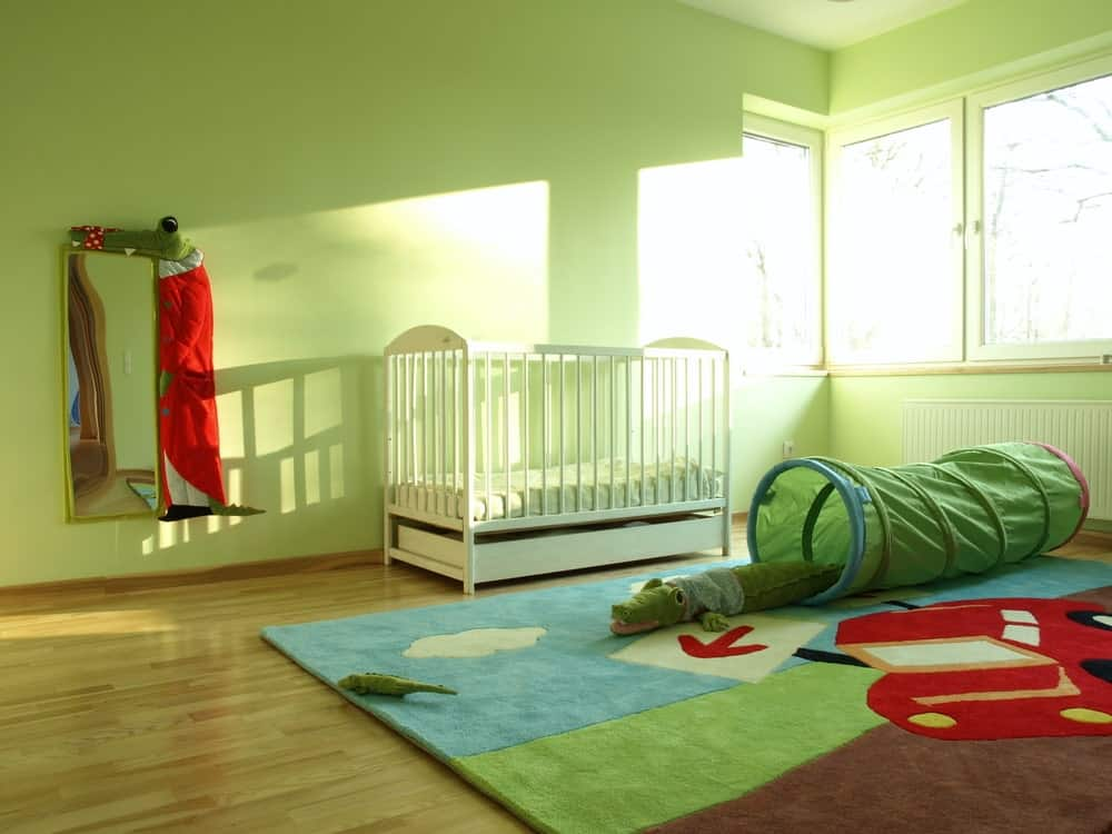 Large nursery room with green walls and hardwood flooring along with a colorful rug.