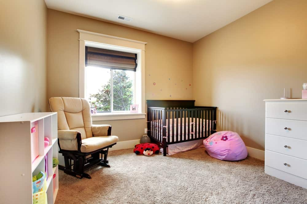 Nursery room with beige walls and a thick carpet flooring.