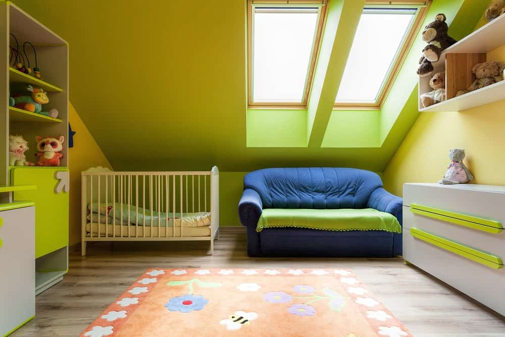 Small nursery room with green shade and a blue couch along with a hardwood flooring topped by a colorful rug.