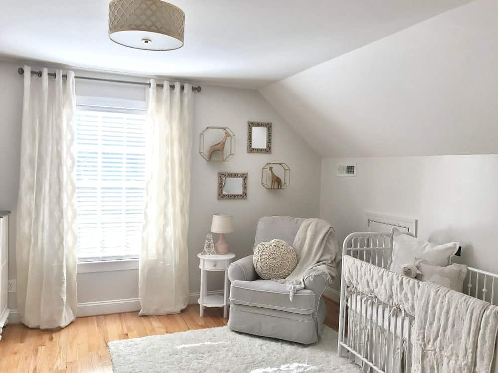 Small nursery room with white walls and a hardwood flooring topped by a rug.