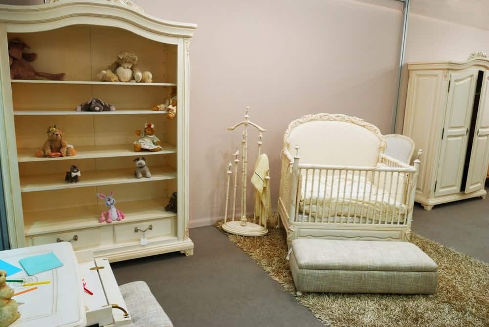 This nursery room features pink walls and dark gray carpet flooring with a rug.
