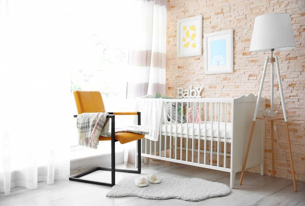 Modish nursery room with a stylish wall and a gray finished flooring.