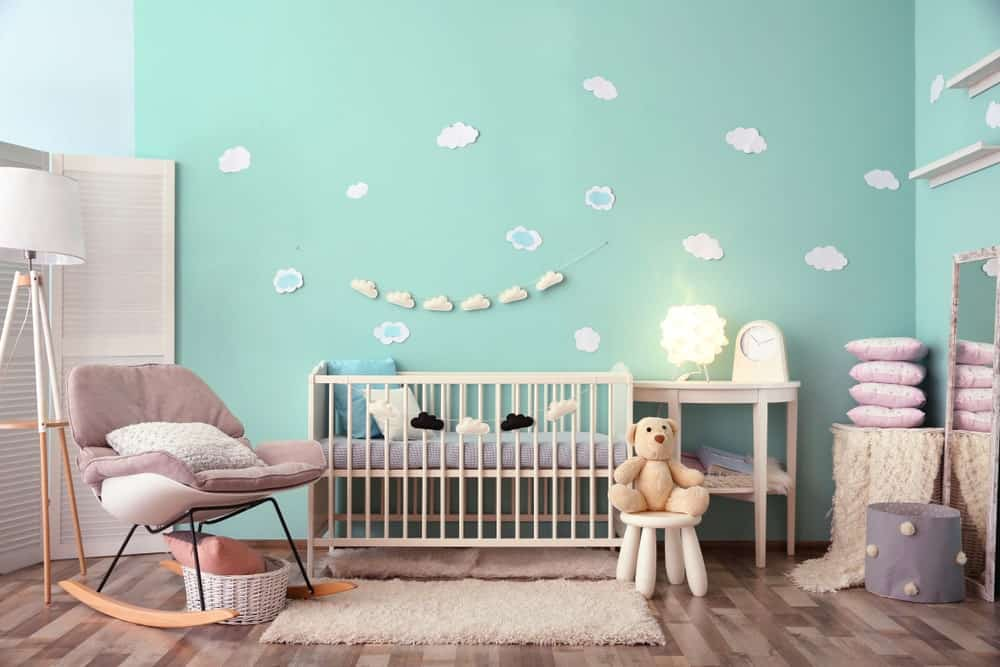 Bright nursery room with green walls with white clouds design and brown hardwood flooring.
