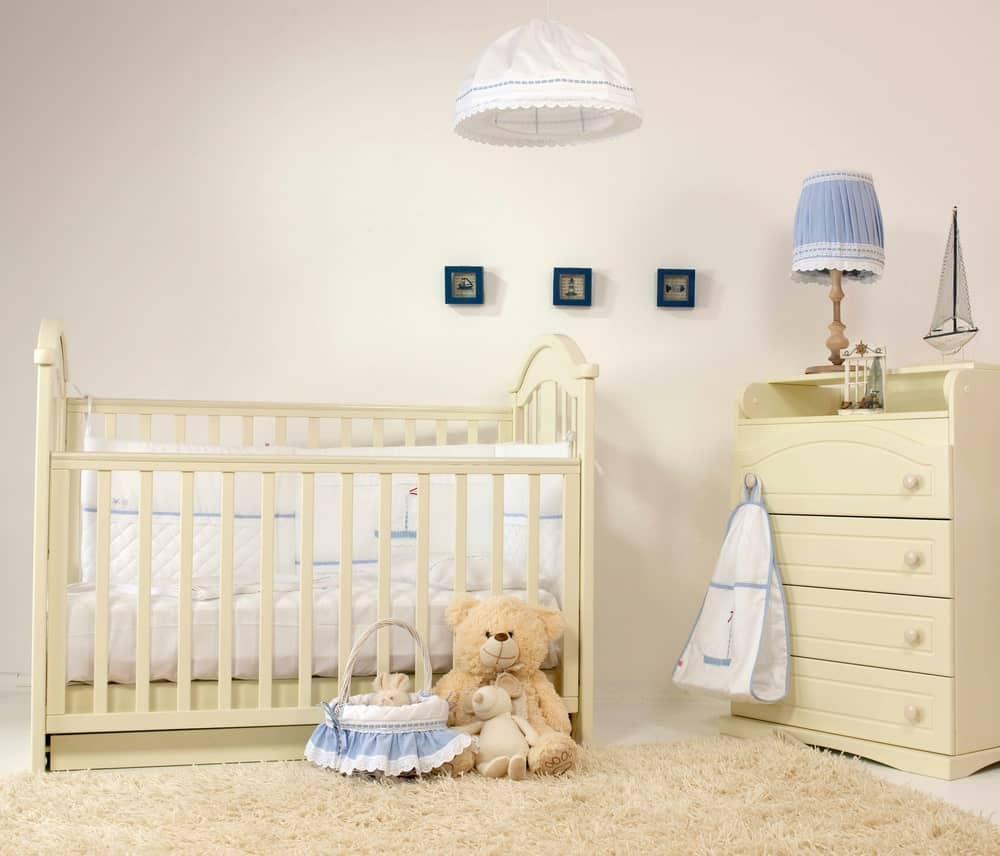 This nursery room features white walls and a brown rug.