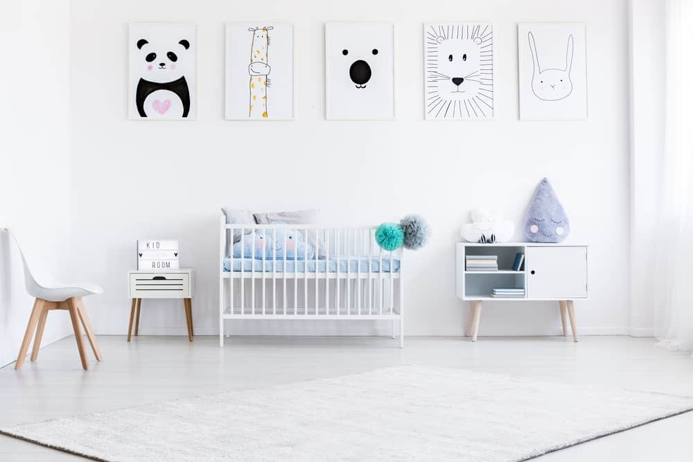 Bright nursery room with white walls with multiple cute decors along with white flooring topped by a white rug.